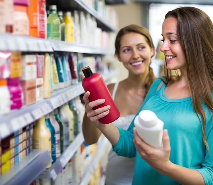 Woman choosing shampoo at store.